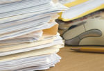stack of documents near mouse